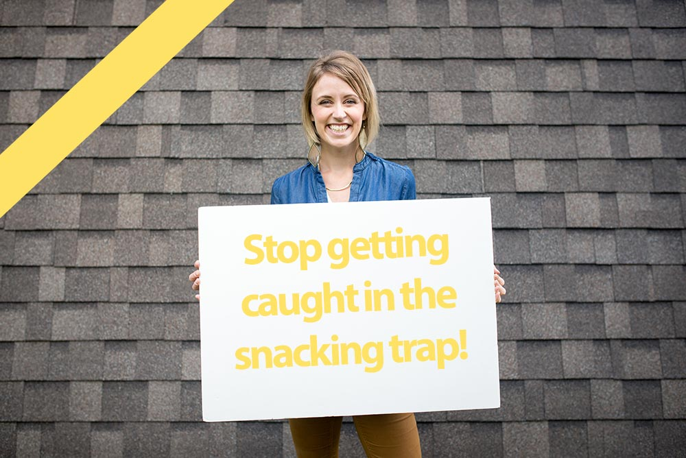 "Jessica holding sign that says ""stop getting caught in the snacking trap!"""
